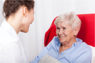 elderly woman having a conversation with her caregiver