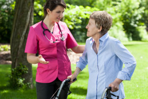 caregiver assisting elderly woman in walking