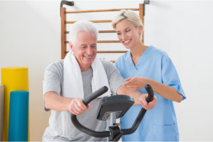 elderly man doing bicycle work out with the caregiver