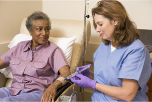 caregiver giving elderly woman medication by intravenous injection